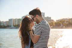 Young happy couple at seaside touching with their noses. Portrait of young happy couple at seaside touching with their noses Royalty Free Stock Images