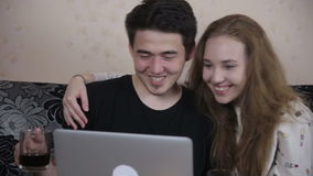 Young happy Couple Sharing a Laptop, kissing, smiling. stock video