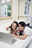 Young happy couple sharing laptop on sofa Stock Images