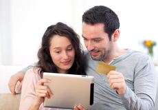 Young happy couple shopping on a tablet Stock Photography