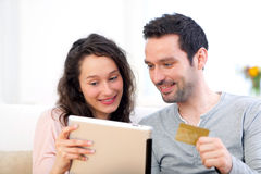 Young happy couple shopping on a tablet Royalty Free Stock Images
