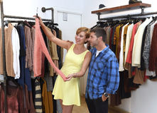 Young happy couple shopping together clothes at fashion shop smiling satisfied in love gift Stock Photos