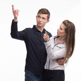 Young happy couple showing presentation pointing on placard over Stock Photos