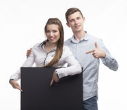 Young happy couple showing presentation pointing on placard over Stock Images