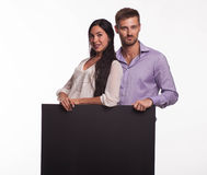 Young happy couple showing presentation pointing placard Stock Photos