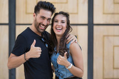 Young happy couple showing thumbs up. Front portrait of young happy couple showing thumbs up Royalty Free Stock Image