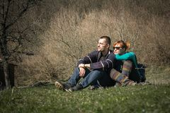 Young happy couple siting in the park enjoying the day together. royalty free stock photos