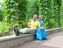 Young happy couple sits in the arbour twined greens Royalty Free Stock Image