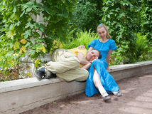 Young happy couple sits in the arbour twined greens Royalty Free Stock Photos