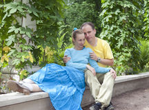 Young happy couple sits in the arbour twined greens Stock Photo