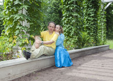 Young happy couple sits in the arbour twined greens Stock Image