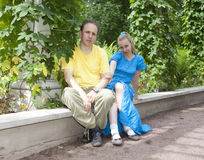 Young happy couple sits in the arbour twined greens Stock Photography
