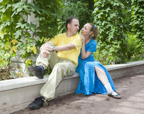 Young happy couple sits in the arbour twined greens Stock Images