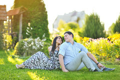 Young happy couple sitting back to back Stock Photos