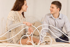 Young happy couple sitting chatting on a bed Stock Images