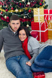 Young happy couple sitting on the floor next to the Christmas tr. Young smiling couple at Christmas night together royalty free stock photography