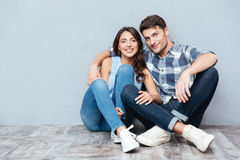 Young happy couple sitting on the floor over gray bakground Stock Photo