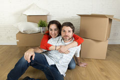 Young happy couple sitting on floor together celebrating moving in new flat house or apartment Stock Photo