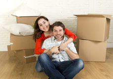 Young happy couple sitting on floor together celebrating moving in new flat house or apartment Royalty Free Stock Photos