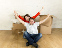 Young happy couple sitting on floor together celebrating moving in new flat house or apartment Stock Photography