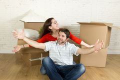 Young happy couple sitting on floor together celebrating moving in new flat house or apartment Royalty Free Stock Photo