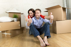 Young happy couple sitting on floor together celebrating moving in new flat house or apartment Stock Photos