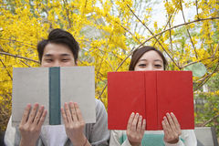Young happy couple sitting side by side and reading their books, face partially obstructed, outdoors in springtime Royalty Free Stock Photo