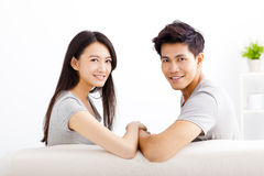Young happy couple sitting on the sofa Royalty Free Stock Images