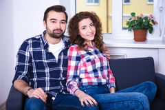 Young happy couple sitting on sofa in living room Stock Photos