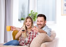 Couple watching tv and laughing. Young happy couple sitting on sofa, watching tv and laughing. Happy and relaxed expression on faces Stock Photo