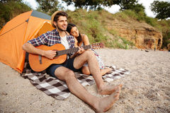 Young happy couple sitting at the tent and playing guitar Royalty Free Stock Images