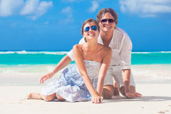 Young happy couple sitting on tropical beach Royalty Free Stock Photo