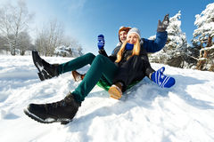 Young happy couple sledding in winter Royalty Free Stock Photo