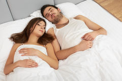 Young Happy Couple Sleeping in Bed Royalty Free Stock Images