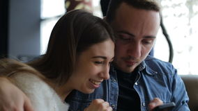 Young happy couple with smartphone in cafe stock footage