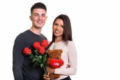 Young happy couple smiling while holding red roses and teddy bea