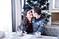 Young happy couple smiling looking at each other and kissing. Christmas tree Stock Image
