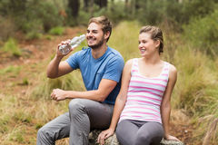 Young happy couple smiling while sitting on a stone. In the nature Stock Photography