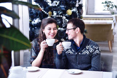 Young happy couple smiling to each other and holding cups.  Christmas tree Royalty Free Stock Photography
