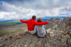 Travel Lifestyle and survival concept rear view. Young happy couple in snowy mountains against sky. Atmospheric moment for lovers in the mountains royalty free stock photo