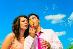 The young happy couple  with soapy bubbles. The young happy couple blowing soapy bubbles  and  having fun  outdoor Royalty Free Stock Images