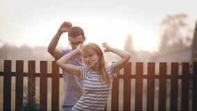 Young happy couple standing on the backyard and having fun together. Cheerful man and woman dancing outside. stock video