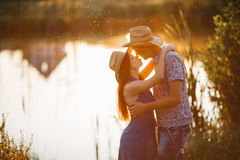 Young happy couple standing close face to face and touching by noses. Pretty brunette girlfriend with long hair and boyfriend with Royalty Free Stock Image