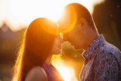 Young happy couple standing close face to face and touching by noses. Pretty brunette girlfriend with long hair and boyfriend with Stock Image