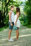 Young happy couple standing in green park Royalty Free Stock Photos