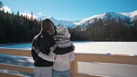 Young Couple is Standing near Mountain Lake in Winter Admiring Landskape. Young Happy Couple is Standing near Mountain Lake in Sunny and Snowy Winter Looking at stock video