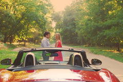 Young happy couple standing near red car Stock Photography