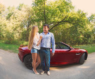 Young happy couple standing near red car Stock Photo
