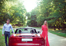 Young happy couple standing near red car Royalty Free Stock Photography