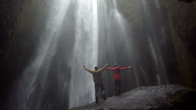 Young happy couple standing under beautiful waterfall Gljufrabui in Iceland and raises hands, feeling freedom and joy stock video footage